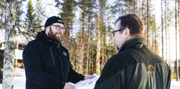 Metsänomistaja ja hankintaesimies metsässä.